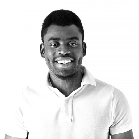Cropped shot of smiling handsome young casually dressed African man model in white polo shirt smiling showing his teeth against studio background with copy space for your promotional information